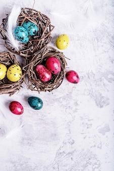Concetto di vacanza di pasqua. uova di quaglia colorate di pasqua con le piume in un nido su fondo di marmo grigio con lo spazio della copia