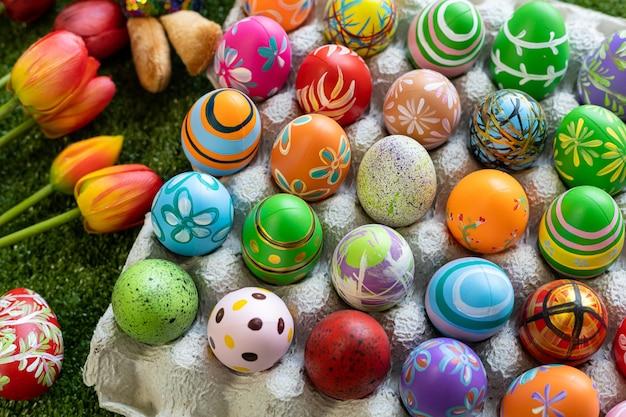 Concetto di vacanza di pasqua, uova di pasqua colorate in scatola di uova, cesto uova di pasqua, cesto di caramelle, bambola di coniglio in fondo di erba verde con spazio.