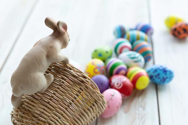 Concetto di vacanza di pasqua, statue di coniglio ornamenti da giardino sul cesto con uova di pasqua colorate su fondo di legno rustico di colore pastello bianco con spazio.