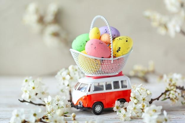 Concetto di vacanza di pasqua - auto giocattolo che trasporta uova di pasqua colorate in un cesto durante il periodo di fioritura