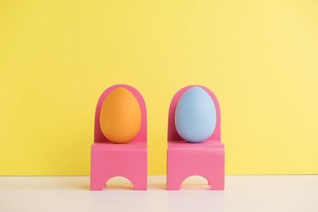 Concetto di vacanza di pasqua con vita di uova carine. diverse emozioni e sentimenti. uova adorabili delle coppie che si siedono sulle sedie rosa sulla parete gialla.