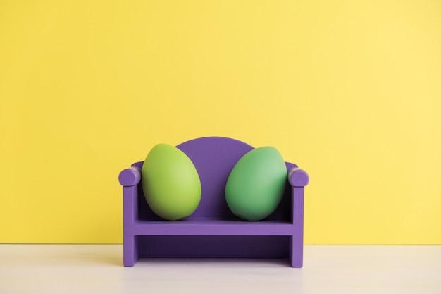 Concetto di vacanza di pasqua con vita di uova carine. diverse emozioni e sentimenti. uova adorabili delle coppie che si siedono sul sofà.