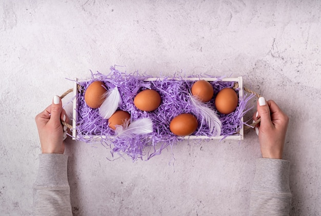 Concetto di vacanza di pasqua. la donna passa la tenuta della scatola di legno bianca con le uova di gallina su fondo di marmo bianco vista dall'alto laici piatta