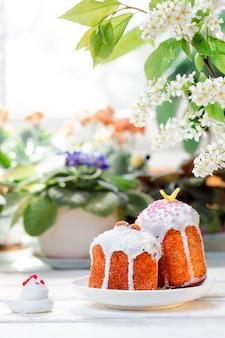 Vacanze di pasqua. due pani pasquali decorati su un piatto accanto a una figurina di pollo. sullo sfondo piante e fiori. orientamento verticale.