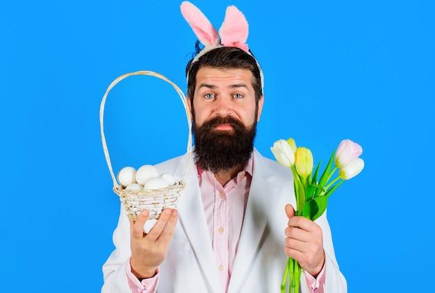 Vacanze pasquali. uomo barbuto in abito con cesto di uova. maschio con cesto di uova e bouquet di tulipani.