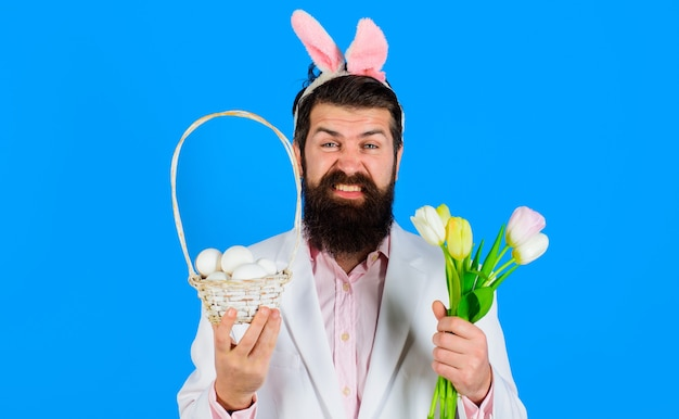 Vacanze di pasqua, uomo barbuto con orecchie da coniglio con cesto di uova e bouquet di tulipani. uomo coniglietto, caccia alle uova.