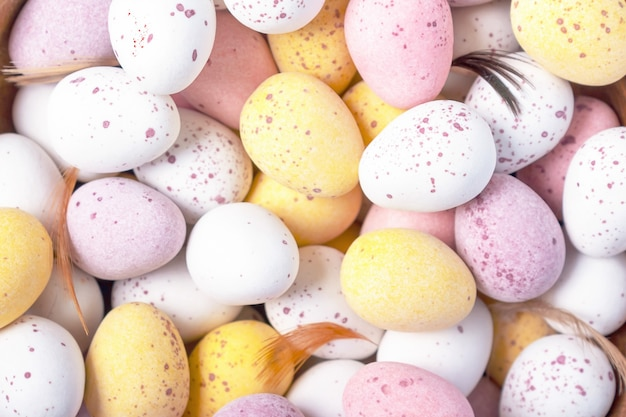 Decorazione di vacanze di pasqua. fondo decorativo variopinto divertente delle uova di pasqua di cioccolato. avvicinamento. vista dall'alto. uova rosa gialle bianche per il trattamento di pasqua.