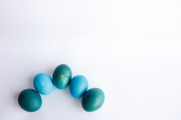 Pasqua, vacanze, tradizione, stile e concetto di minimalismo - fila di uova di pasqua blu ombre isolate su sfondo bianco