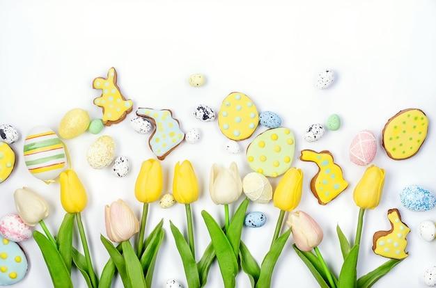 Biscotti di pan di zenzero fatti in casa di pasqua con glassa, uova decorate e tulipani su sfondo bianco