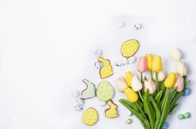 Biscotti di pan di zenzero fatti in casa di pasqua con glassa, uova decorate e tulipani su un bianco