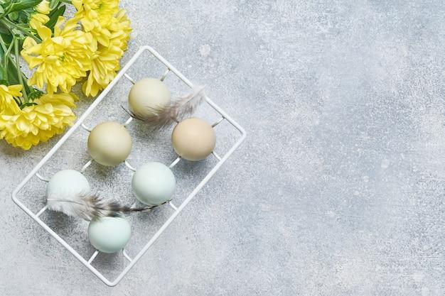 Uova di pasqua azzurre in supporto in metallo vintage bianco e fiori di crisantemi gialli su sfondo grigio. vista dall'alto.