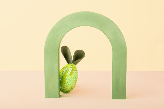 Carta di concetto minimale di pasqua con spazio di copia coniglio divertente dall'uovo e dalle orecchie che si nascondono dietro un arco