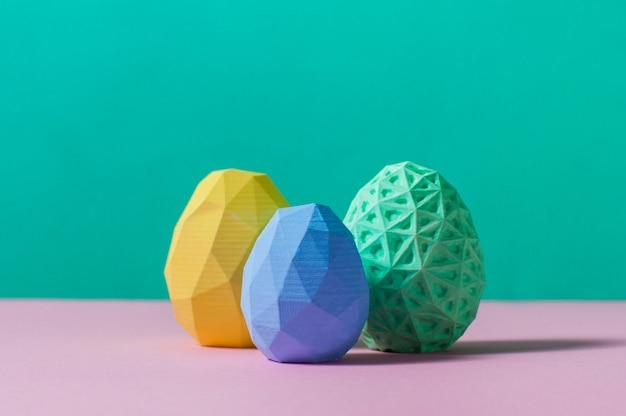 Concetto di arredamento minimalista di pasqua. colore delle uova di pasqua geometriche su sfondo turchese e rosa con uno spazio vuoto per il testo.