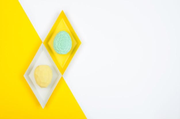 Concetto di arredamento minimalista di pasqua. uova di pasqua con motivo geometrico su blocchi di colore sfondo con uno spazio vuoto per il testo. vista dall'alto, piatto.