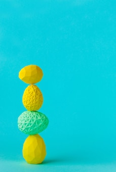 Concetto di arredamento minimalista di pasqua. uova di pasqua geometriche in piedi una sopra l'altra sulla parete blu con uno spazio vuoto per il testo.