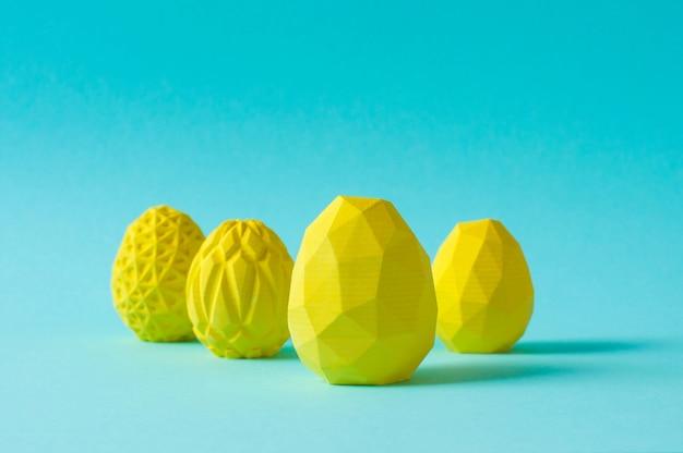 Concetto di arredamento minimalista di pasqua. uova di pasqua geometriche gialle su fondo blu con uno spazio vuoto per testo.