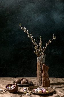 Umore pasquale ancora in vita con rami di salice in fiore in vaso di ceramica, coniglio al cioccolato tradizionale, uova e dolci sul tavolo con carta stropicciata.