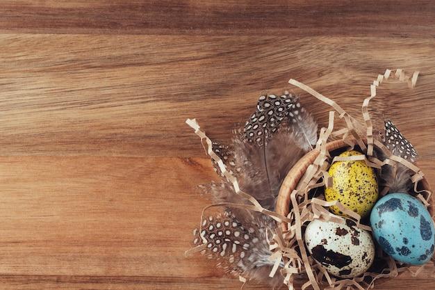 Nido di pasqua fatto di fieno con uova colorate dipinte e piume su uno sfondo di legno. appartamento piatto, vista dall'alto, copia spazio. sfondo di pasqua. concetto di pasqua in un tradizionale stile retrò.