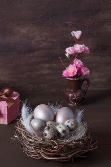 Nido di pasqua con uova su bakcground marrone con fiori rosa e confezione regalo