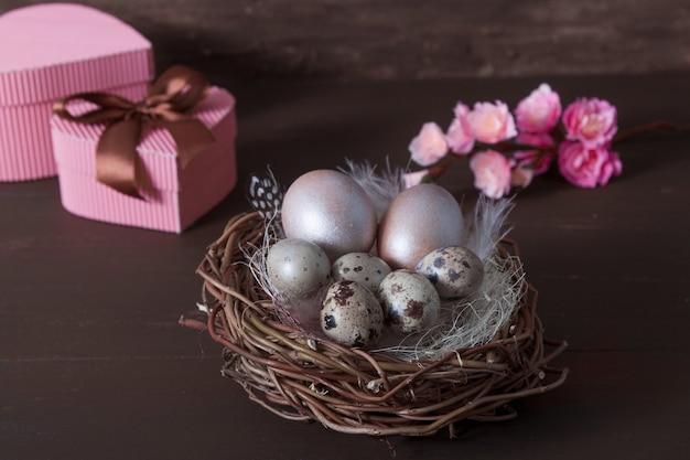 Nido di pasqua con uova su bakcground marrone con fiori rosa e scatole regalo