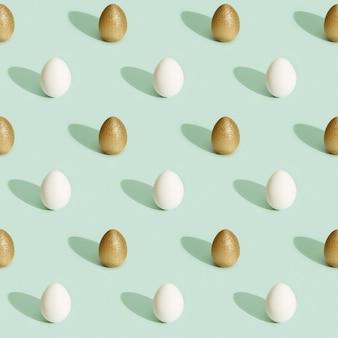 Modello di pasqua con uova luminose, uova colorate e bianche dorate lucide su carta verde