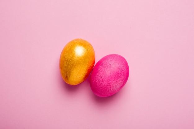 Uova di pasqua e oro rosa su una superficie rosa