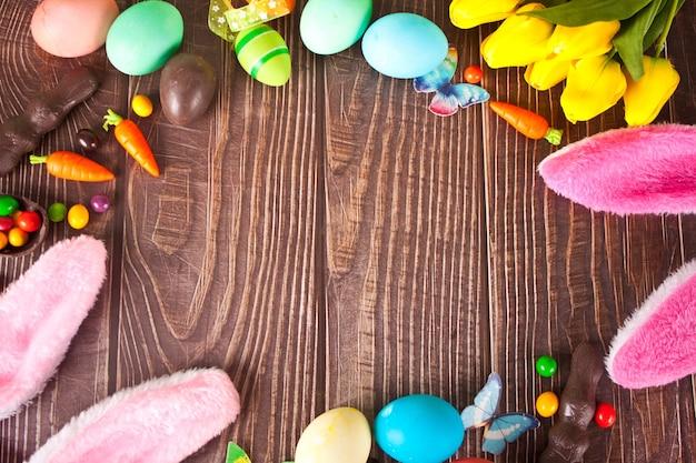 Cornice di pasqua con uova colorate, tulipani, orecchie da coniglio, carote sui precedenti di legno. vista dall'alto. copia spazio.