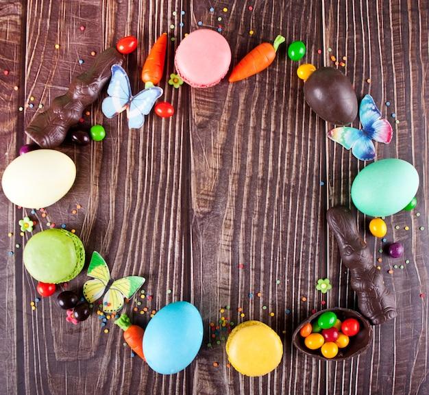 Cornice di pasqua con uova colorate, tulipani, coniglietto di cioccolato, carote sullo sfondo di legno. vista dall'alto. copia spazio.