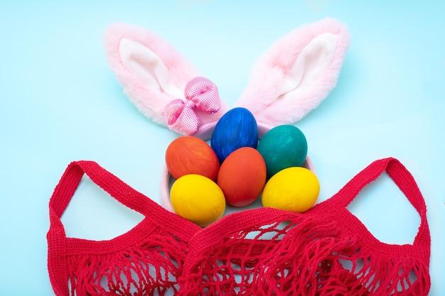 Concetto di acquisto di pasqua. uova di pasqua dipinte a mano, orecchie da coniglio rosa e una borsa della spesa rossa su sfondo blu