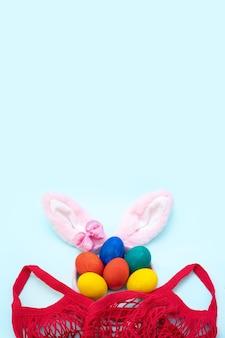 Concetto di acquisto di pasqua. uova di pasqua dipinte a mano, orecchie da coniglio rosa e una borsa della spesa rossa
