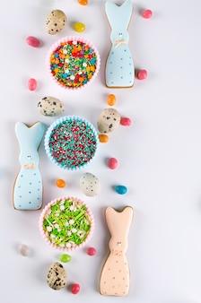 Composizione decorativa in primavera di pasqua. preparare biscotti di zucchero fatti in casa. biscotto a forma di coniglio divertente, strumenti necessari per fare la pasta di pan di zenzero, granelli colorati.