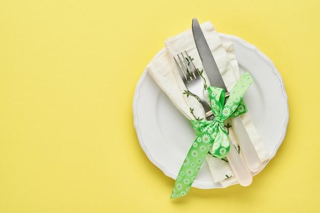 Regolazione della tabella di saluto di primavera di pasqua con confezione regalo con nastro verde, uova e carota dolce sulla tabella dei colori di tendenza gialla. vista dall'alto. spazio per il testo.