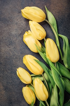 Superficie di pasqua con tulipani gialli. biglietto di auguri per la festa della mamma. copia spazio