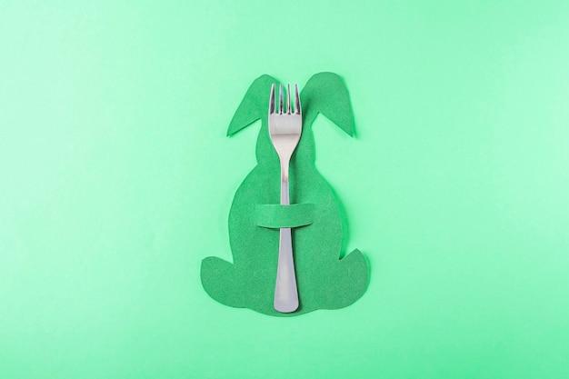 Regolazione della tavola di pasqua. simpatico portaposate creativo divertente a forma di coniglio verde su sfondo verde. creatività fai da te e per bambini. sfondo di pasqua con copia spazio per il testo.