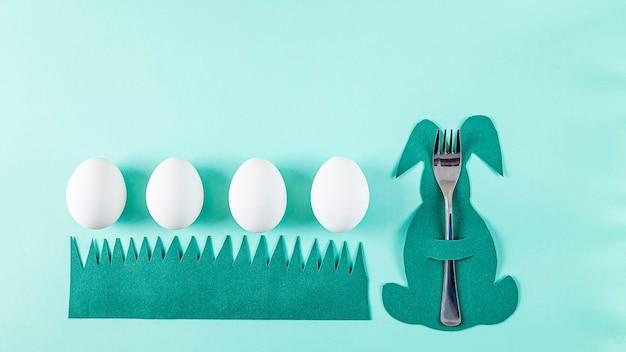 Regolazione della tavola di pasqua. simpatico portaposate creativo divertente a forma di coniglietto verde e uova bianche su sfondo verde. creatività fai da te e per bambini. sfondo di pasqua con copia spazio per il testo