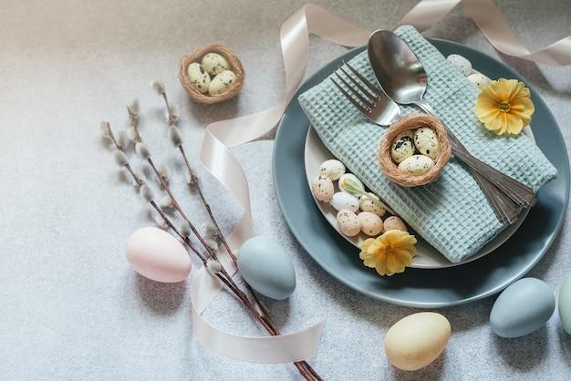 Idee per la tavola di pasqua, decorazioni minime: uova di pasqua, rami di amento di salice, nido d'uccello