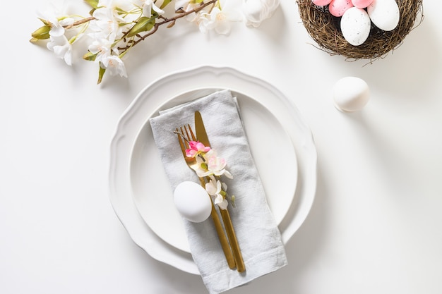 Regolazione della tavola di pasqua con i fiori di fioritura della mela sulla tavola bianca.