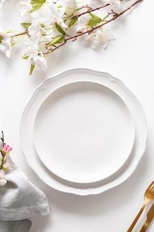 Regolazione della tavola di pasqua con fiori che sbocciano sulla tavola bianca.