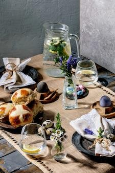Regolazione della tavola di pasqua con uova colorate e di cioccolato, focacce incrociate calde, bouquet di fiori