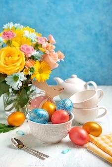 Regolazione della tavola di pasqua con uova di pasqua e fiori primaverili. buona pasqua. sfondo di pasqua di congratulazioni.