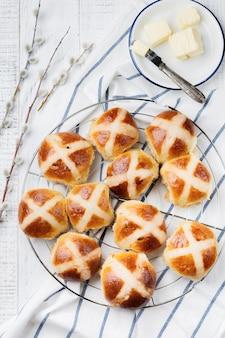 Pasqua tradizionale hot cross panini fatti in casa sul vassoio in legno con tessuto di lino e rami di salice su bianco di legno