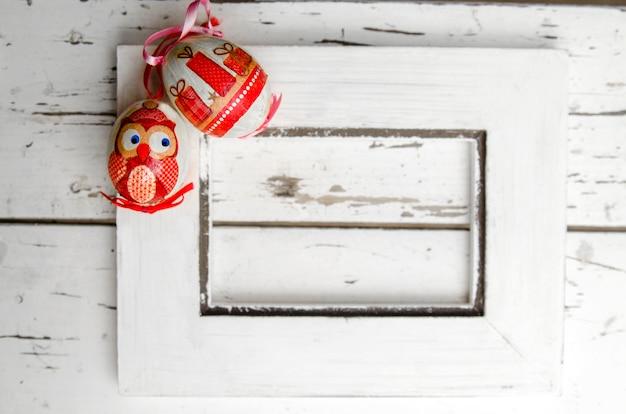 Uova d'annata di pasqua su struttura di legno vuota. abbraccio sulla parete rustica bianca