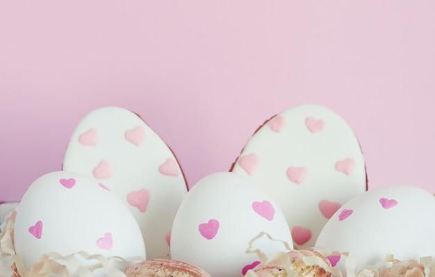 Uova bianche di pasqua con cuori rosa, pan di zenzero a forma di uova con cuori su uno sfondo rosa.