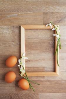 Struttura decorata ad est con le uova di pasqua e fiori sulla tavola rustica di legno, fondo di festa per la vostra decorazione. concetto di festa di pasqua e della primavera con lo spazio della copia.