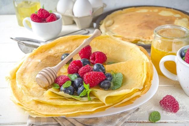Vacanza tradizionale di maslenitsa dell'europa orientale. cucinare frittelle di crepe, con ingredienti, miele e frutti di bosco freschi