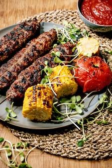 Fast food orientale. kebab di lyulya di manzo piccante alla griglia su bastoncini su pane piatto con verdure grigliate pannocchia di mais dolce, pomodoro e paprika, salsa di pomodoro sul tavolo di legno.