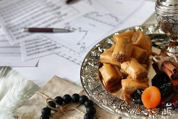 Tavolo di dolci orientali su un piatto d'argento baklava e snack al tamarindo sul posto di lavoro