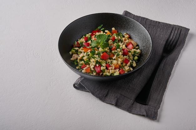 Tabbouleh di insalata tradizionale orientale fatto di bulgur o couscous carne di pollame prezzemolo menta al buio