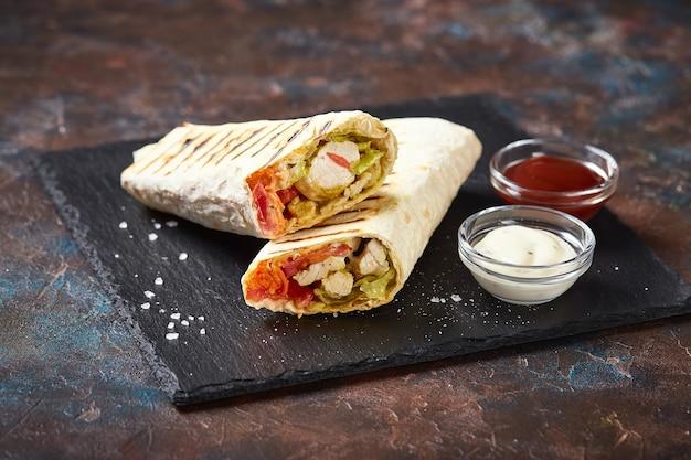 Shawarma tradizionale orientale con pollo e verdure, doner kebab con salse