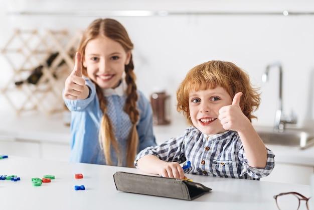 Facile ed educativo. fratelli brillanti motivati entusiasti che sembrano abbastanza soddisfatti dopo aver risolto indovinelli di matematica giocando insieme a speciali giochi educativi
